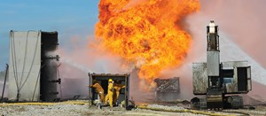 Well control specialists install a capping stack on a burning oil well in an environmentally sensitive region.